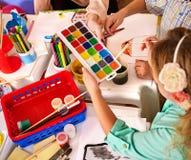 Små studenter flicka och pojkemålning i konstskolagrupp arkivfoto