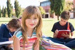 Små studenter på skolauniversitetsområdet arkivfoto