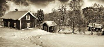Små stugor i gammalt lantligt vinterlandskap Arkivfoto