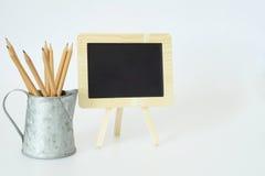 Små svart tavla och blyertspennor Arkivbild