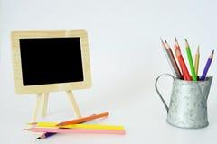Små svart tavla- och färgblyertspennor Arkivbilder