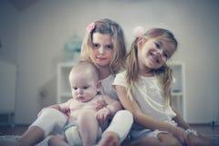 Små systrar poserar till kameran med behandla som ett barn brodern Arkivfoto