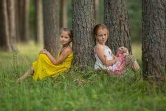 Små systrar sitter nära ett träd i parkera Natur royaltyfri foto
