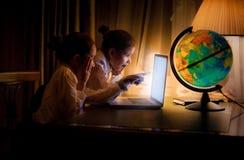 Små systrar som använder bärbara datorn på natten Arkivbilder