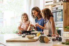 Små systrar som lagar mat med hennes moder i köket arkivbild