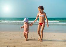 Små systrar som promenerar stranden Arkivbild