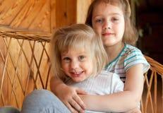 Små systrar som sitter omfamna sig Arkivfoton