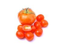 Små tomater för stora tomater på vit bakgrund arkivbilder