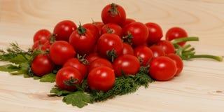 Små tomater och nya örter på träbakgrund Royaltyfria Bilder