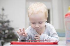 Små två år flicka använder en minnestavla på en soffa Royaltyfri Fotografi