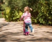 Små två år gammal flicka som rider hennes sparkcykel Arkivfoto