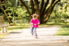 Små två år gammal flicka som rider hennes sparkcykel Arkivbilder