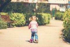 Små två år gammal flicka som rider hennes sparkcykel Royaltyfri Foto