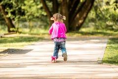 Små två år gammal flicka som rider hennes sparkcykel Royaltyfria Bilder