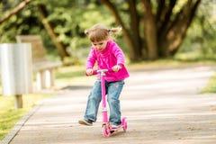 Små två år gammal flicka som rider hennes sparkcykel Fotografering för Bildbyråer