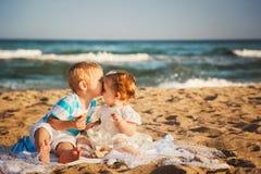 Små ungar är kyssande och ha gyckel på stranden tillsammans nära havet, lyckligt livsstilfamiljbegrepp arkivbilder