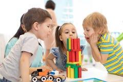 Små ungar bygger hemmastadd kvarterleksaker eller daycare Emotionella ungar som spelar med färgkvarter Bildande leksaker för royaltyfria bilder