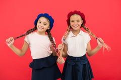 Små ungar för skolflickafransman som ler framsidan som poserar röd bakgrund för hatt Hur man bär den franska basker Baskerstilins arkivfoto