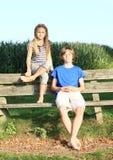 Små ungar - flicka- och pojkesammanträde på en bänk Arkivbild