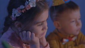 Små ungar sitter på den röda tabellen med kakan Lycklig grupp av barn på födelsedagpartiet arkivfilmer