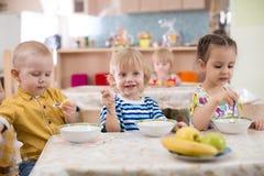 Små ungar som äter i dagis royaltyfri foto