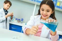 Små ungar som lär kemi i hällande flytande för skolalaboratorium arkivfoton