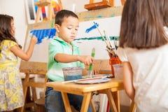 Små ungar som målar i konstgrupp Arkivfoto