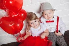 Små ungar som upp rymmer och väljer hjärta, sväller Valentin dag och förälskelsebegrepp, på vit bakgrund Royaltyfri Bild