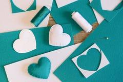 Små välfyllda hjärtaleksaker Hjärtor som göras av filt, tråden, filt täcker, visaren på trätabellen Enkla handgjorda hantverk Royaltyfri Foto