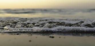 Små vågor på stranden under solnedgång royaltyfri bild
