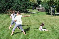 Småbarn gör sportövningar på gräset i parkera arkivfoton