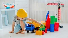 Småbarn 4 gamla år och att spela med ett stort antal färgrika plast- leksaker i rummet, konstruktion av olikt royaltyfri foto