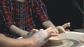 Småbarn lär att arbeta på ett hjul för keramiker` s barnet gör hans första hantverk från lera lager videofilmer