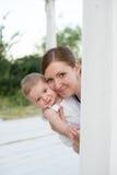 Småbarn med hennes moder i vit Arkivbild