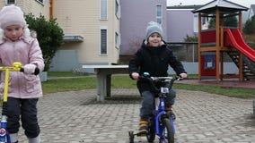 Småbarn rider en mini- sparkcykel och en cykel på lekplatsen lager videofilmer