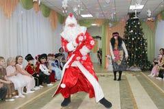 Småbarn ser som den Santa Claus dansen på ferie i dagiset - Ryssland, Moskva, December 17, 2016 Royaltyfri Fotografi