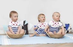 Småbarn sitter på en vit bakgrund som ler seamless tema för blått marin- hav royaltyfri foto