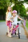 Småbarn som lär att rida en cykel i en stad, parkerar på solig sommarafton Gulliga små flickor som rider en cykel Arkivfoton