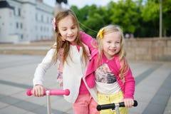 Småbarn som lär att rida sparkcyklar i en stad, parkerar på solig sommarafton Gulliga små flickor som rider rullar Arkivfoton