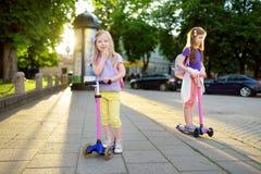 Småbarn som lär att rida sparkcyklar i en stad, parkerar på solig sommarafton Gulliga små flickor som rider rullar Royaltyfria Bilder