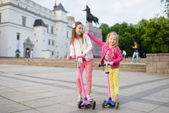 Småbarn som lär att rida sparkcyklar i en stad, parkerar på solig sommarafton Gulliga små flickor som rider rullar Royaltyfri Bild
