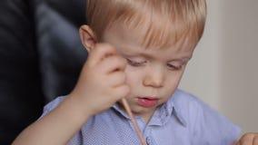 Småbarnattraktioner med en borste och en målarfärg Närbild lager videofilmer