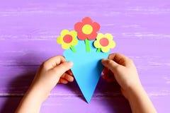 Småbarnet gjorde hantverk för pappers- blommor för dag eller födelsedag för moder` s Barnhåll och shower en pappers- bukett arkivfoto