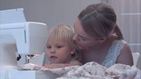 Småbarnet lär ny kunskap med hennes moder som använder symaskinen arkivfilmer