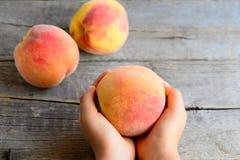 Småbarnet rymmer en mogen persika i hans händer Söta läckra persikor på en gammal trätabell Royaltyfri Foto
