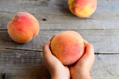 Småbarnet rymmer en mogen persika i hans hand Saftiga ljusa persikor på en gammal trätabell Läcker och vitaminefterrätt för barn Arkivfoton