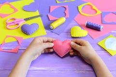 Småbarnet rymmer en rosa filthjärta i hans händer Barnet visar hjärtahantverk Hantverkhjälpmedel och material på en trätabell Royaltyfria Foton
