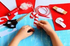 Småbarnet rymmer rottingen för julfiltgodisen i hans händer Barnet gjorde en filtgodisrotting Sy tillförsel för att skapa juldeko Arkivbild