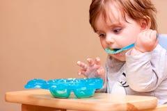 Småbarnet sitter på en tabell och äter Arkivfoton