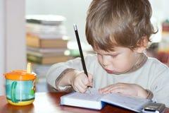 Småbarnet skriver vid blyertspennan Royaltyfri Foto